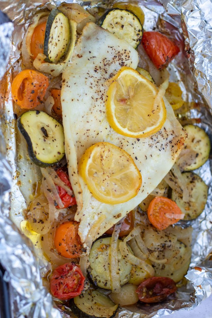 A single piece of white fish in foil, surrounded by roasted cherry tomatoes that are yellow, red and orange, sliced zucchini and caramelized onions. The fish is baked in the oven in a foil packet. Two slices of lemon are on top of the fish