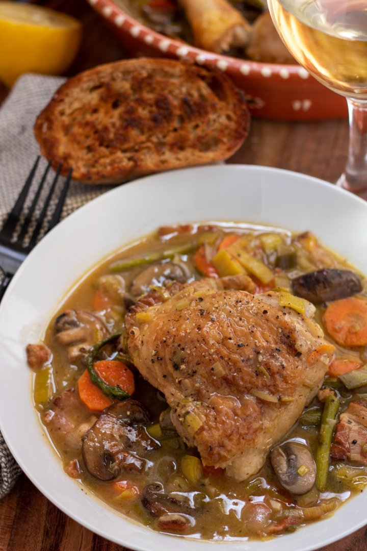 A white round dish with a piece of chicken in white wine sauce with spring vegetables. There's a glass of white wine, a piece of crusty bread and a half of a lemon in the background