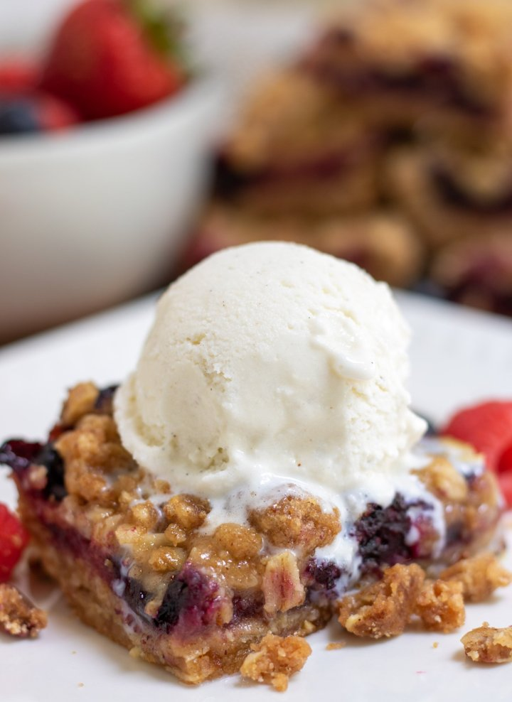 A square white dish with a berry crumble bar that's topped with a scoop of vanilla ice cream that's slightly melted. There's a bowl of berries and more crumble bars in the background