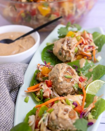 3 lettuce wraps topped with a chicken meatball, mango slaw and peanut sauce. There is a small white bowl of peanut sauce in the background and large bowl of colorful mango slaw
