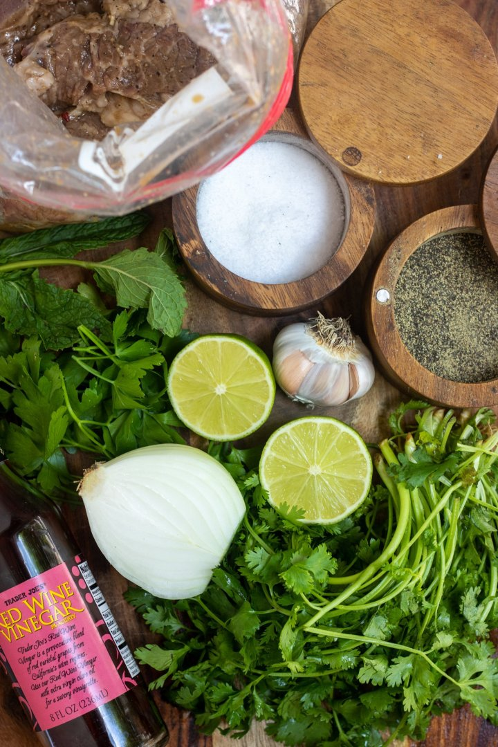 A wooden background with ingredients for chimichurri sauce: a bunch of parsley and cilantro, halved lime, whole onion, a whole garlic clove, and salt and pepper cellars