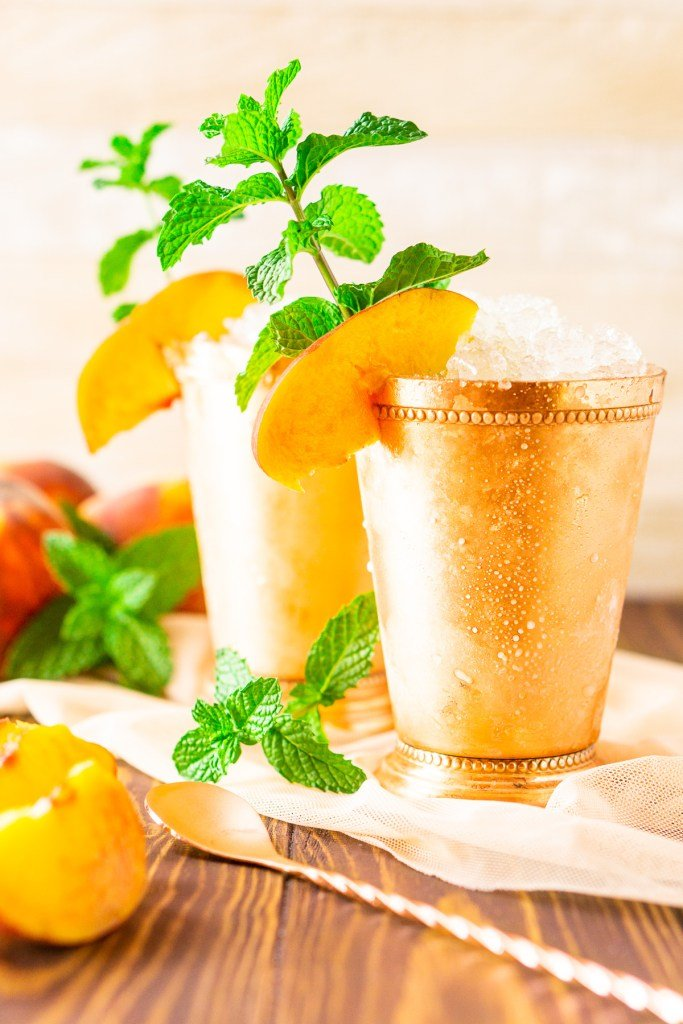 Two copper cups with peach mint julep.  The cups are ice cold and sweating.  There's a fresh peach slices and mint sprig for garnish.  There's fresh sliced peaches and extra mint in the background.