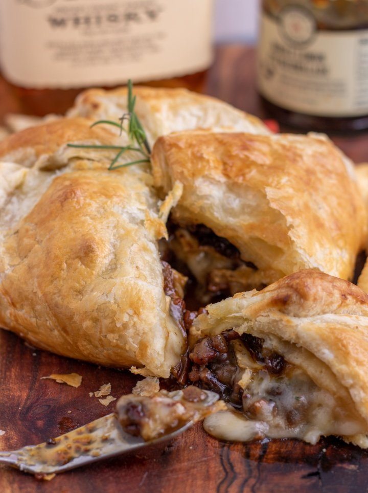 A wooden cutting board with a baked brie wrapped in puff pastry on top. The baked brie is cut into a wedge and there's melted cheese falling out of the side with pecans. It's topped with a sprig of rosemary and there's a bottle of whisky and jar of fig jam in the background