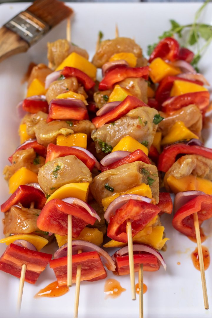 A white platter with raw marinated chicken skewers stacked on top of each other. They're brushed with a sweet chili glaze that's dripping onto the platter. There's a pastry brush in the corner.