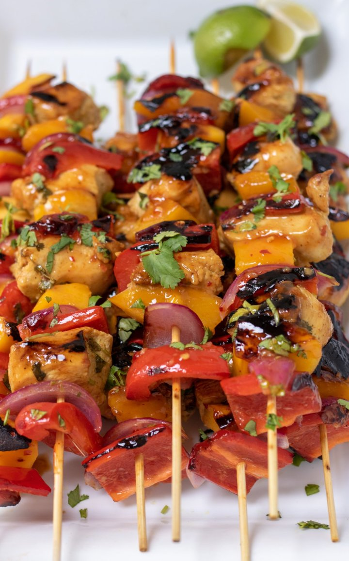 A white platter stacked withgrilled chicken and mango kabobs. They're sprinkled with fresh chopped cilantro and there's a piece of lime in the background.