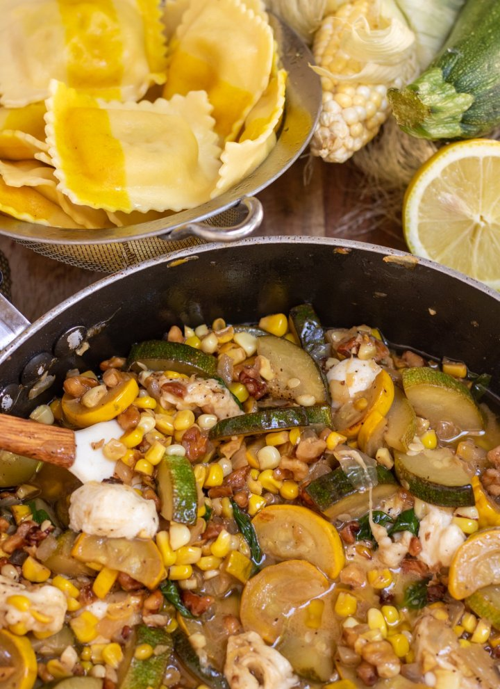 A large saute pan filled with sauteed zucchini, corn and onions with melted mozzarella. Theres' a strainer of sweet corn ravioli in the background with a whole ear of corn