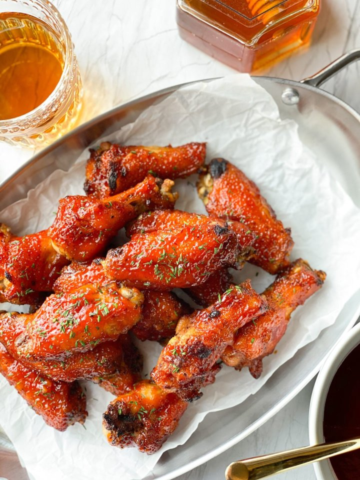 A serving platter piled with spicy honey bourbon wings. There's a side of honey in the background. The wings are on white parchment paper and they're crispy with a sweet and spicy glaze