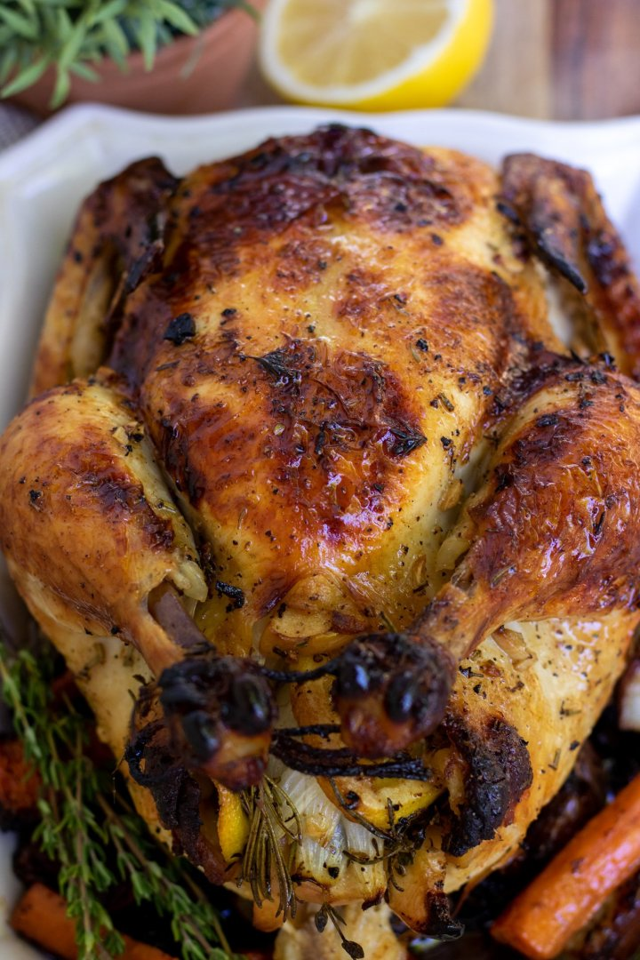 A whole chicken that's been roasted until golden and browned. The skin looks crispy and browned. There's fresh sage and a half of a lemon in the background.