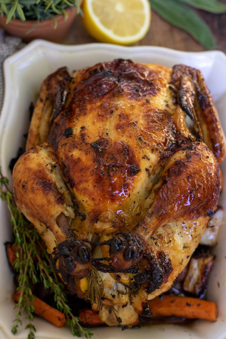 A whole roasted chicken on square white serving dish. The legs are tied up and the skin is browned and golden. There's a bunch of fresh rosemary and thyme next to the chicken and it's sitting on top of carrots, potatoes and onions.