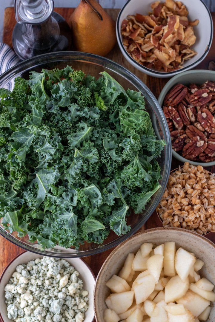A large glass bowl of chopped kale, a small bowl of toasted pecans, a small bowl of Gorgonzola cheese crumbles, a bowl of cooked farro, a brown speckled bowl of sliced pears, and a small green bowl of cooked bacon that's crumbled.
