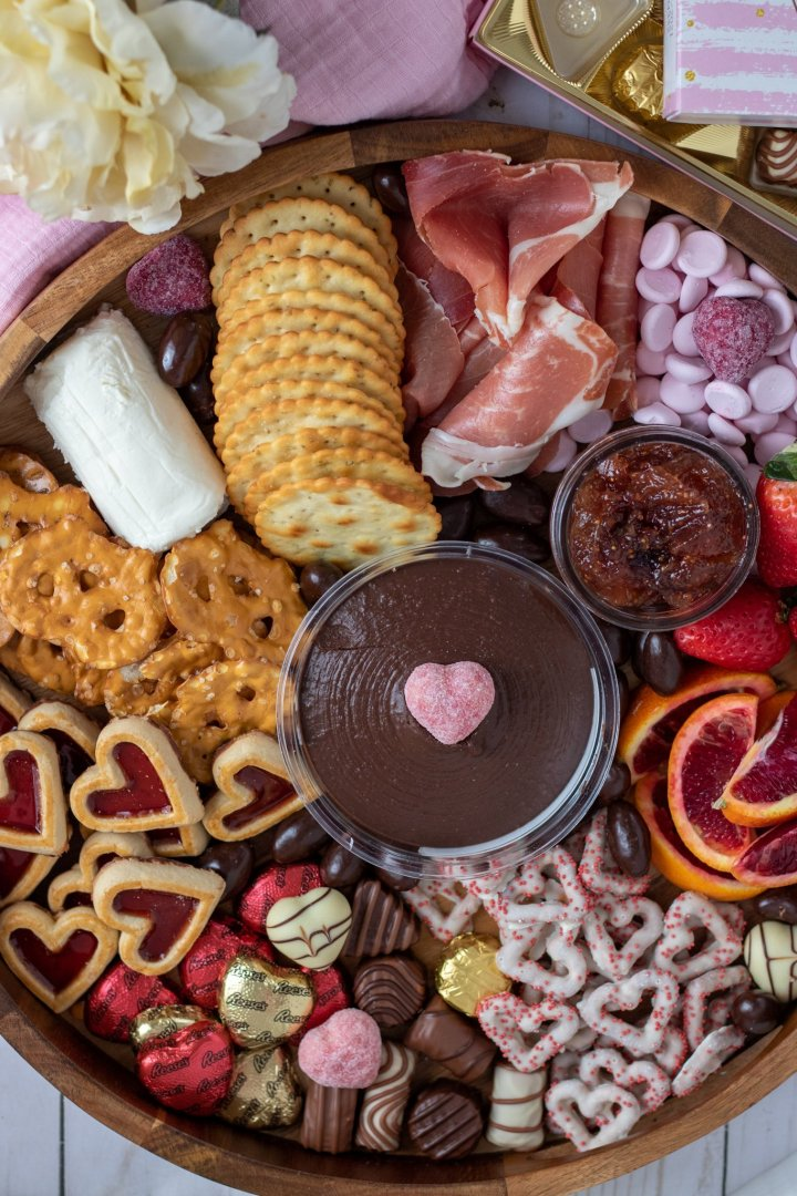 A valentine's day charcuterie with heart shaped cookies, chocolates and fruit.