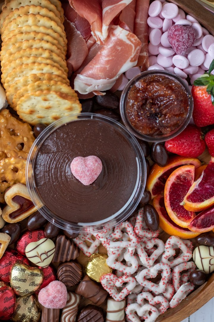 A charcuterie board for valentine's day with chocolates, strawberries, prosciutto,candies, pretzels and chocolate hummus in the middle.