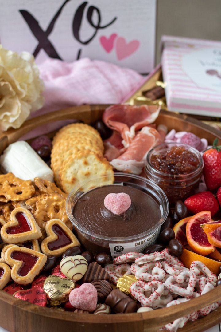 A round wooden serving tray filled with crackers, chocolates, heart shaped truffles, prosciutto, blood oranges and strawberries. There's a white flower on a pink cloth napkin with a box of chocolates in the background