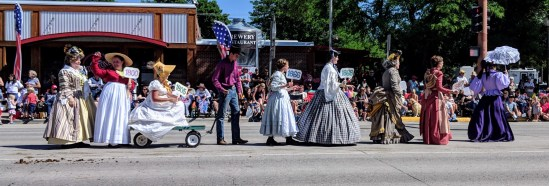 Women wearing period clothing, walking in the Cody 4th of July Parade