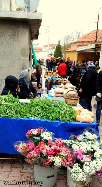 Puestos de frutas, verduras y ramos de flores.