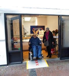 Stadsdeelvoorzitter mw. Van Pinxteren met alleskunner Ton Blans van de adviesraad Amsterdam Centrum Drempelvrij bij het Ijscuipje op de Heiligeweg
