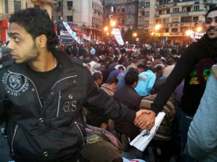 29 Powerful Pictures - Christians protecting Muslims during prayer during the 2011 uprisings in Cairo, Egypt.
