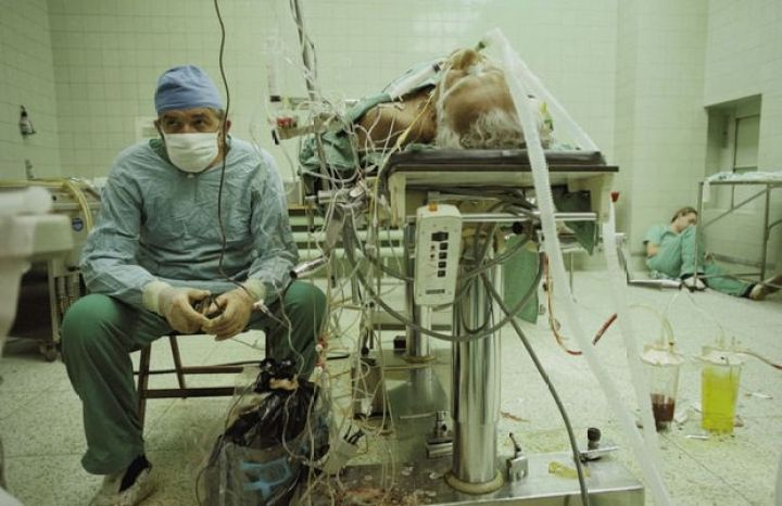 29 Powerful Pictures - In 1987, Dr. Religa monitors his patient's vitals after a intensive 23-hour long heart transplant surgery. His assistant is resting in the corner.