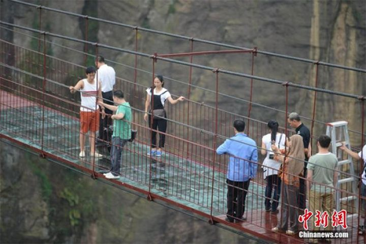 Glass Bridge in China - There are actually staff that help tourists cross the glass section and give them encouragement to make it across.