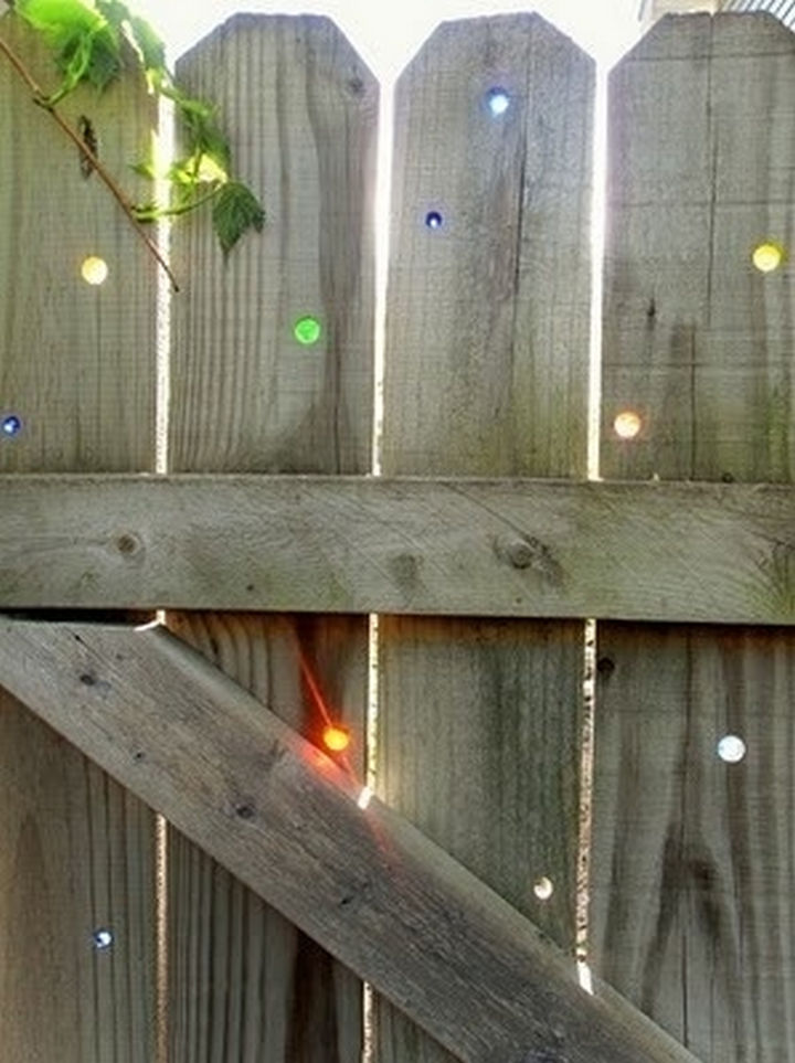 34 DIY Backyard Ideas for the Summer - Put marbles in your fence to fill any holes in your wooden fence.