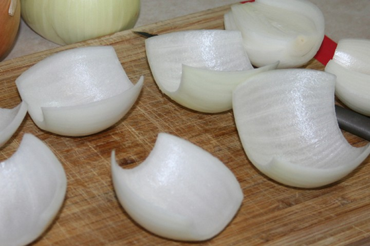 """Begin by peeling the onions and cutting each one in half to make onion """"petals"""" which we'll use to wrap around each meatball."""