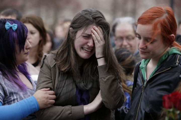 9 Heartbreaking Images - A girl mourns the loss of those in the Boston Marathon bombing.