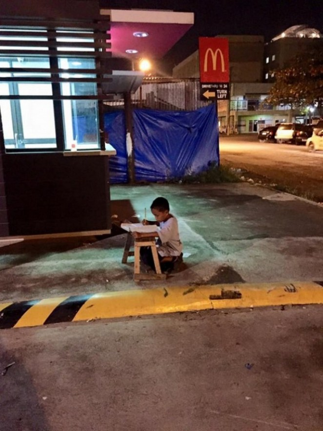 9-year-old Daniel Cabrera completing his homework on a makeshift desk on the pavement and using faint light from a nearby McDonald's restaurant.