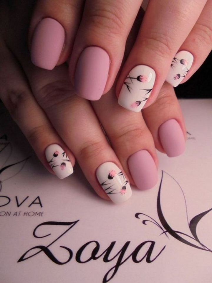 Beautiful matte pink manicure with delicate flower designs.