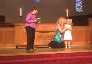 """One of our students is recognized on stage during the """"graduation chapel,"""" as school director, Laurel Zinssar, prepares to present her a Bible."""