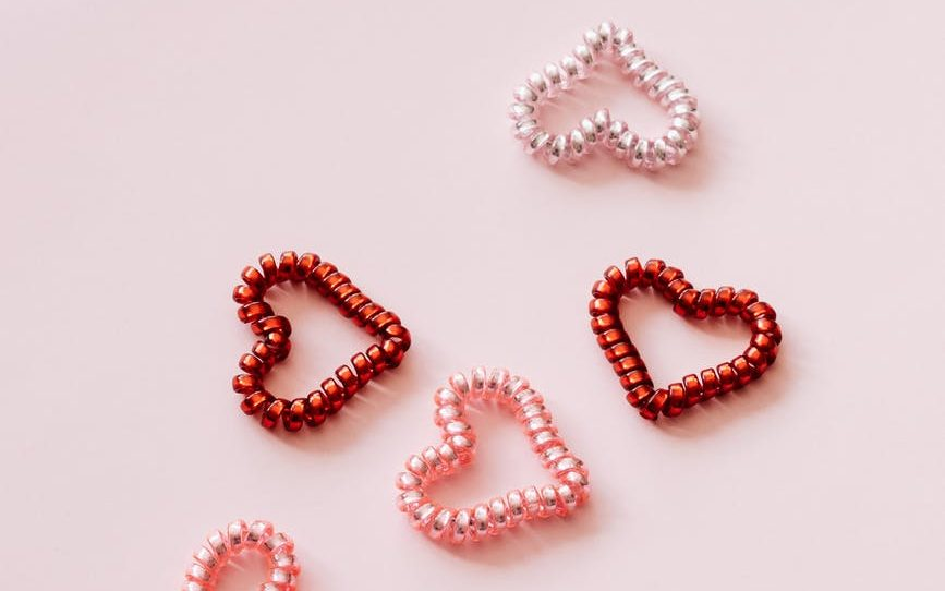 colorful coil hearts on pale pink background