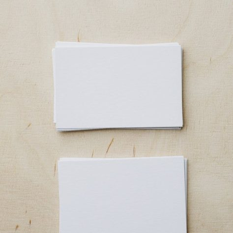 stacks of blank white visiting cards on table