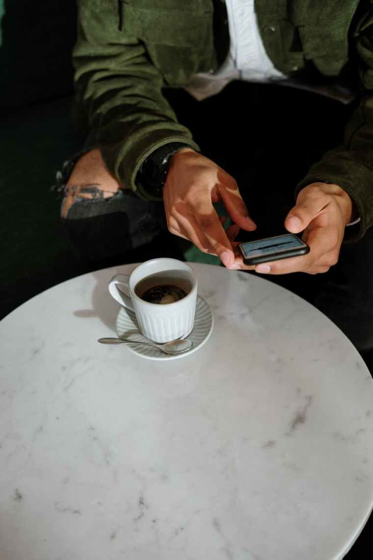 person holding black smartphone near white ceramic cup on white table