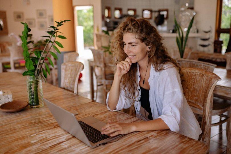 woman in white dress shirt using laptop computer