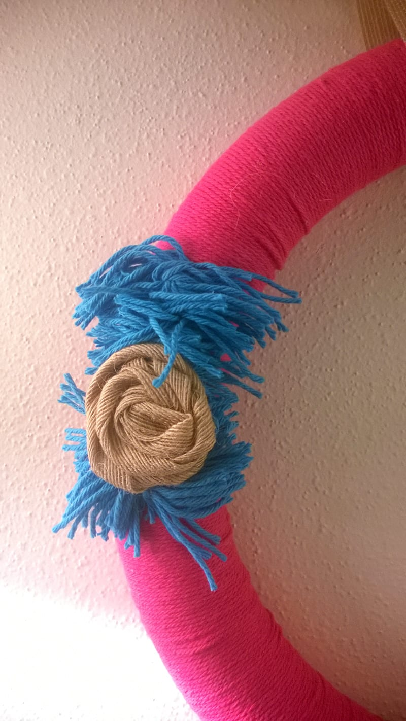 DIY:  Pink and Turquoise Spring Wreath--burlap rosette set on top of turquoise yarn in pom pom shape