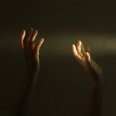 Raised hands with light