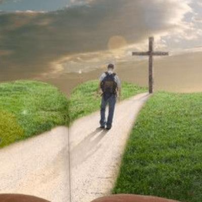 Man walking on road toward cross