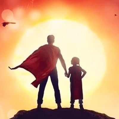 Father and daughter wearing superhero caps silhouetted with sun in background