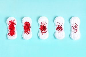 Menstrual pad with red glitter on blue colored background.