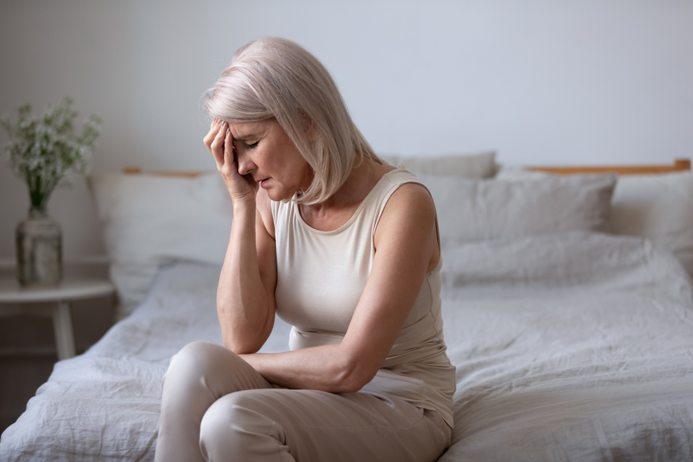 middle aged woman sitting on bed with hand on face