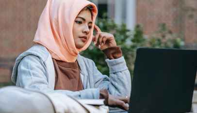 thoughtful young arab woman studying online on netbook in courtyard
