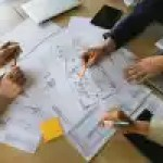 businesspeople with pens in hands examining schemes on papers