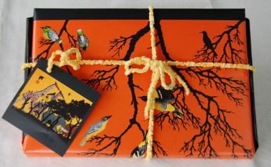 Geschenkpapier aus einem Kalender mit Bildern des afrikanischen Künstlers Timothé Kodjo Honkou. Band von einem frisch gewaschenen, aber leider sich auflösenden Badezimmer Webteppich, den ich reparierte - das Band behielt ich für Geschenke.