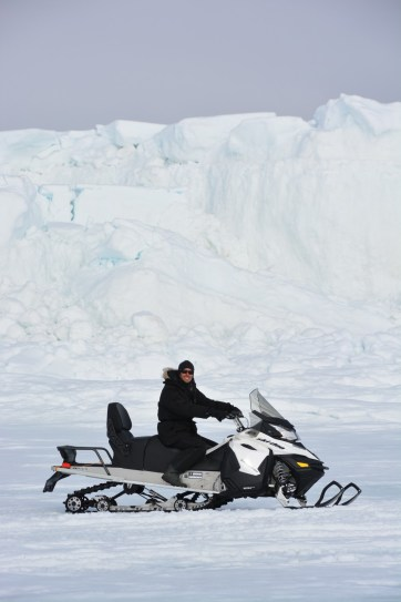 A shot of Adam Garbo on snowmobile with high ice walls produced by low tides (M.St-Amant).