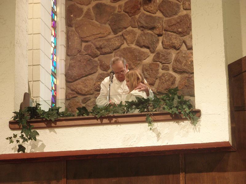 Ted Bartell baptizes his granddaughter,Emily