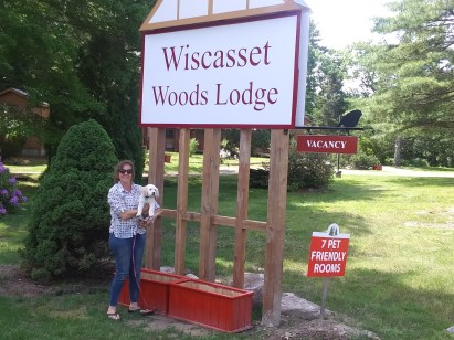 Pet owner with puppy in front of Wiscasset Woods Lodge sign