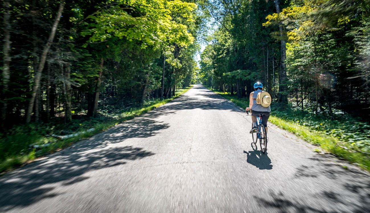 Woman riding bike on empty Washington Island road