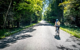 Woman riding bike on empty Washington Island road
