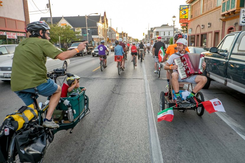Accordion player plays on back of bike during Polish Moon Ride