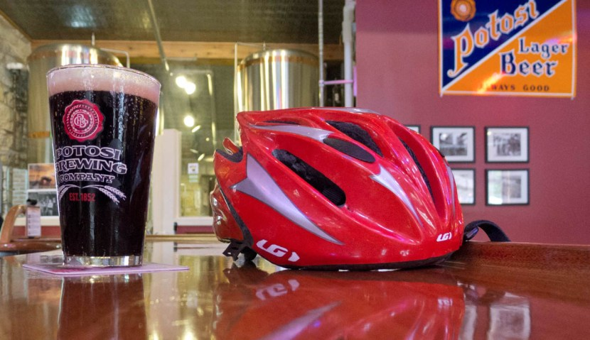 A pint of beer next to a bicycle helmet on a bar in Potosi Brewery tasting room.