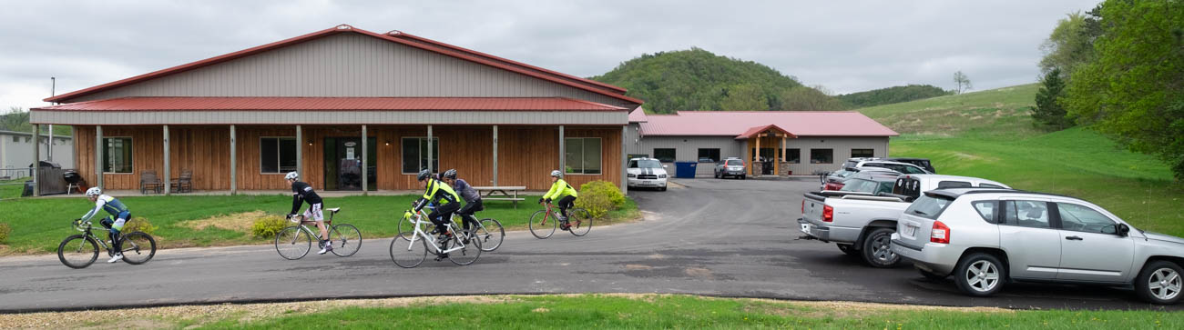 Five people on bikes leave the Borah Teamwear factory for a lunchtime ride